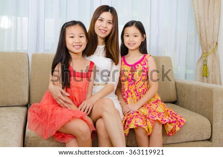 Indoor portrait of beautiful asian mother and her two daughters - stock photo