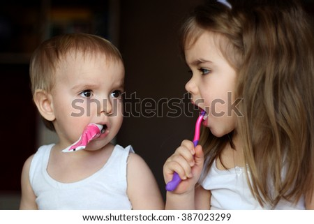 Indoor portrait of cute little kids brushing their teeth and looking on each other, happy family and dental hygiene - stock photo