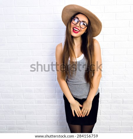 Indoor portrait of cute sweet pretty young woman wearing straw hat and hipster glasses, ready for summer vacation, positive emotions, joy, fun. White urban brick wall background. - stock photo