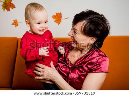 Indoor portrait of grandmother with her grandchild - stock photo