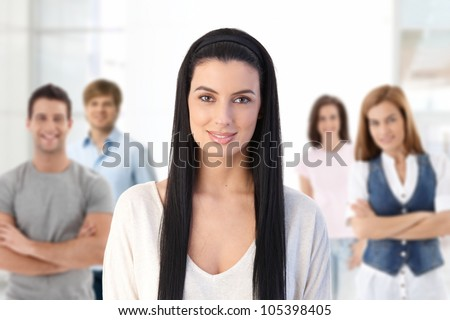 Indoor portrait of group of smiling young people, attractive woman in front looking at camera, smiling. - stock photo