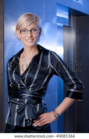 Indoor portrait of happy young businesswoman standing on office corridor, smiling. - stock photo