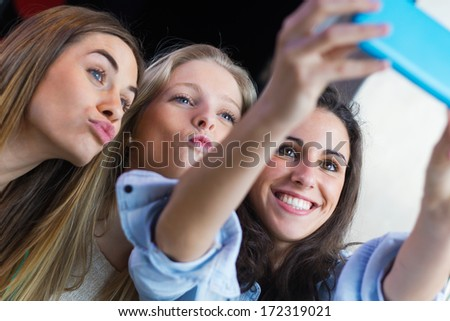 Indoor portrait of three friends taking photos with a smartphone