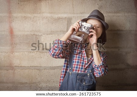 Indoor portrait of woman in a hipster style with vintage camera - stock photo