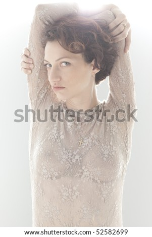 Indoor portrait of woman with arms behind head