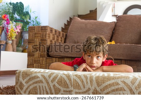 indoor portrait of young boy watching tv at home - stock photo