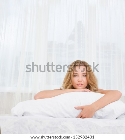 indoor portrait of young caucasian woman sleeping or awaken in bed at home - stock photo