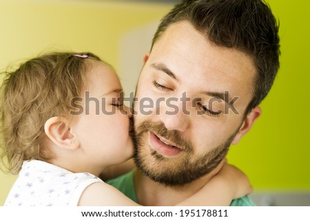 Indoor portrait of young father hugging his little daughter