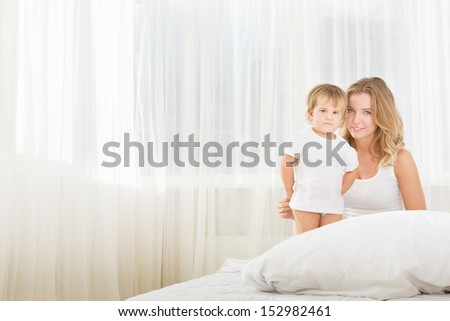 indoor portrait of young happy mother and baby child in bed at home in the morning - stock photo