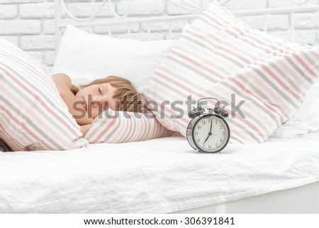 indoor portrait of young happy smiing child girl sleeping in her bed, happy morning time - stock photo