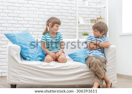 indoor portrait of young happy smiing children, kids, boy and girl, sitting on sofa at home - stock photo