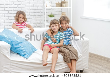 indoor portrait of young happy smiing children, kids, boy and girls, sitting on sofa at home - stock photo