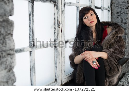 Indoor portrait of young sensual woman sitting on a window sill, horizontal shot - stock photo