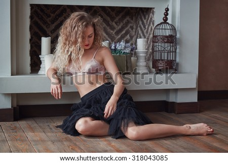 Indoor portrait of young sexy dreaming woman sitting on the floor. Home interior.