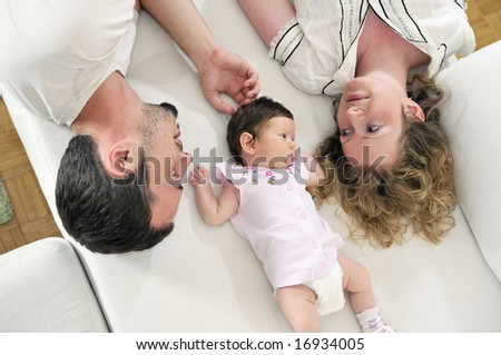 indoor portrait with happy young family and  cute little babby - stock photo
