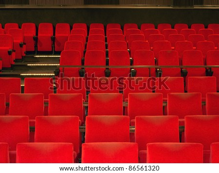 indoor scenery showing a movie theater with red seats in warm ambiance