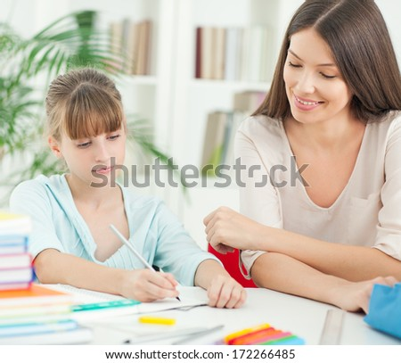 Indoor shot of a smiling mother helping her daughter with the homework. - stock photo