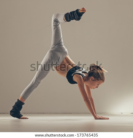Indoor shot of a young blond woman doing yoga.