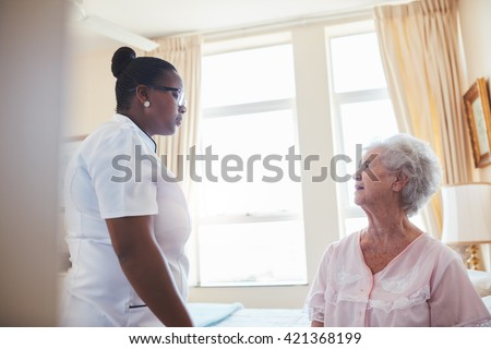 Indoor shot of female doctor visiting her senior patient for routine checkup at home. Nurse talking with old woman sitting on bed. - stock photo