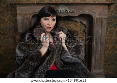 Indoor shot of luxurious woman in fur coat sitting by the fireplace - stock photo