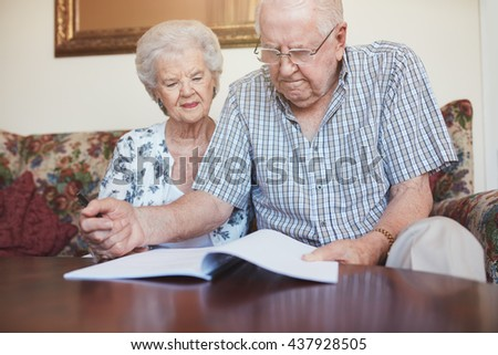 Indoor shot of mature couple at home reading paperwork together. Senior man and woman sitting on sofa going through some retirement paperwork. - stock photo