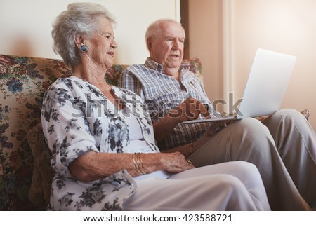 Indoor shot of senior couple sitting on a couch with a laptop computer. Old man and woman relaxing on a sofa using laptop. - stock photo