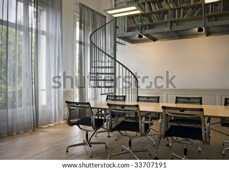 Indoor shot of small office with spiral stairs on background - stock photo