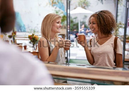 Indoor shot of two young female friends having a cup of coffee at cafe. Women at restaurant drinking hot coffee from disposable cup. - stock photo