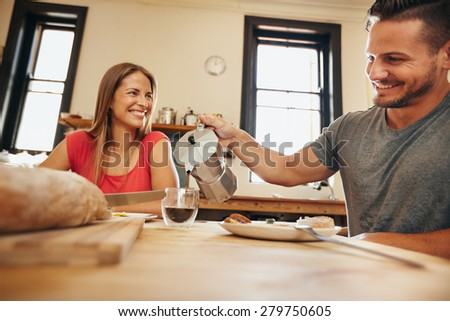 Indoor shot of young man pouring coffee into a cup with his girlfriend having breakfast in kitchen at home. Smiling young couple having breakfast. - stock photo
