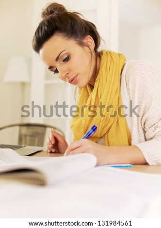 Indoor woman busy writing something and studying all her books - stock photo