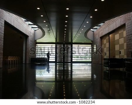 indoors of a modern architecture with reflection and a person looking out of the window