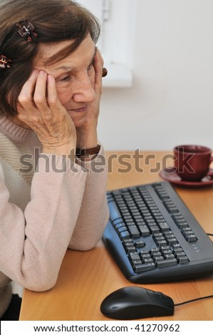 Indoors portrait of worried mature woman siting at computer - stock photo