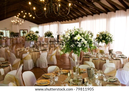 Indoors wedding reception venue with décor, selective focus on flowers - stock photo