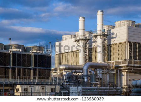 Industiral cooling plant in late afternoon with blue sky - stock photo