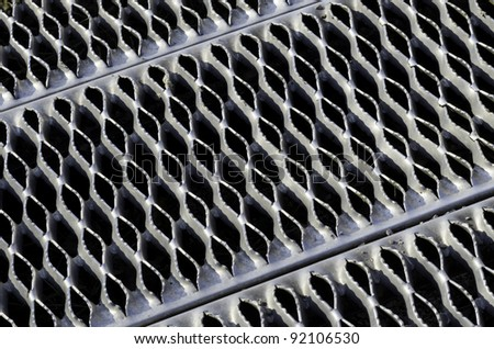 Industrial abstract: Symmetrical safety ramp of aluminum with small ridges, like teeth, to provide traction for pedestrians