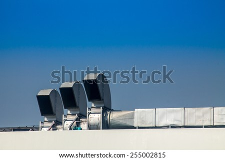 Industrial air conditioning and ventilation systems on a roof,on blue isolated. - stock photo