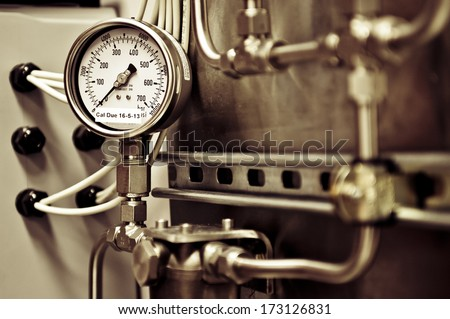 Industrial analogue pressure gage set against pipes and cabling - stock photo