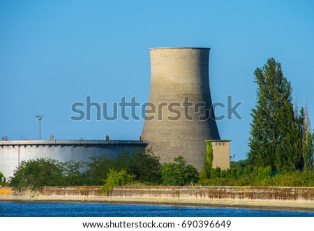 Industrial area and port of Ravenna, Italy, with a cooling tower and an oil tank of a former refinery.