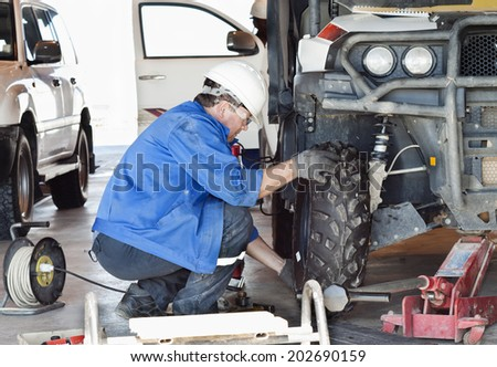 Industrial area. Mechanic in protective clothes repairs the automobile mechanism.