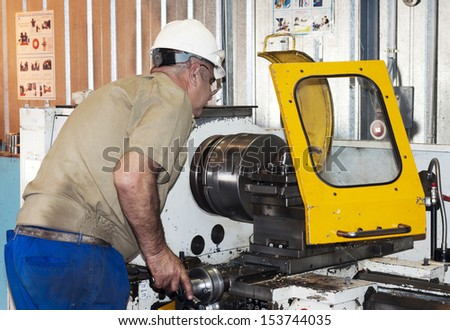 Industrial area. The mechanic works at the lathe.