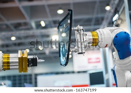 Industrial automated robot arm holding car glass in factory - stock photo