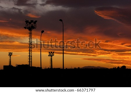 industrial background: Construction site with steel frames rising up against a sunset with cloudy orange sky - stock photo