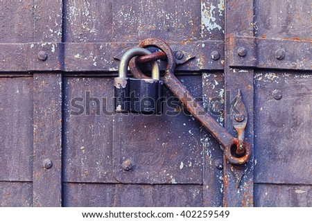 Industrial background - iron old padlock keeping the aged door heck at the rusty riveted door. Selective focus at the padlock and door heck.  - stock photo