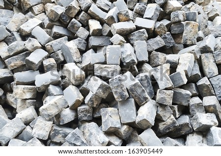 Industrial background - Pile of cobblestone pavers close-up