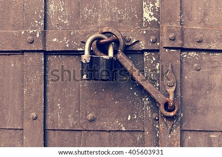 Industrial background - steel black padlock keeping the old door heck at the iron rusty riveted door. Vintage filter applied - stock photo