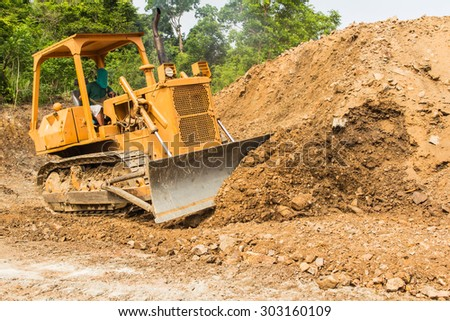 industrial backhoe, bulldozer moving earth and sand in sandpit or quarry - stock photo