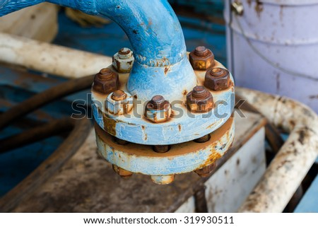 Industrial blue pipelines joint with rust bolts and joints - stock photo