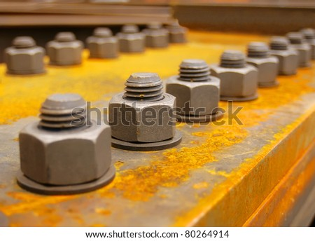 Industrial bolts and nuts with shallow focus - stock photo
