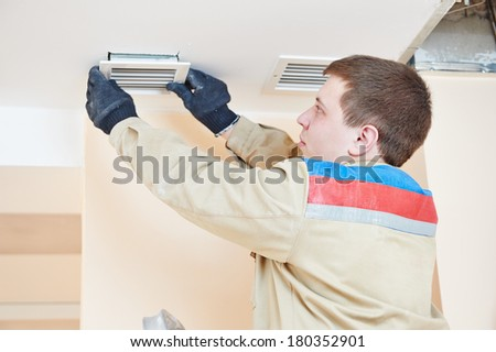 industrial builder installing ventilation or air conditioning filter holder in ceiling - stock photo