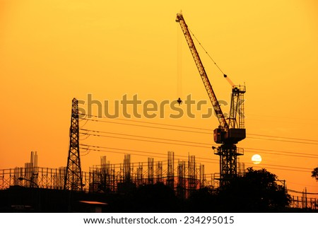 Industrial building site and electric pylon at sunset silhouetted against a colorful orange sky with a crane in the foreground